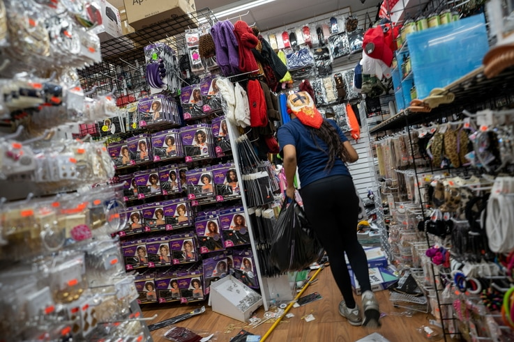 A looter is seen at a beauty supply store that was broken into following protests over the police shooting death of Walter…
