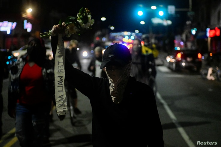 A demonstrator holds a bouquet of flowers during a rally after the death of Walter Wallace Jr., a Black man who was shot by…