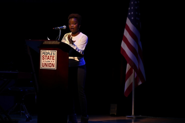 """Activist Karine Jean-Pierre speaks during the """"People's State of the Union"""" event one day ahead of President Trump's State of…"""