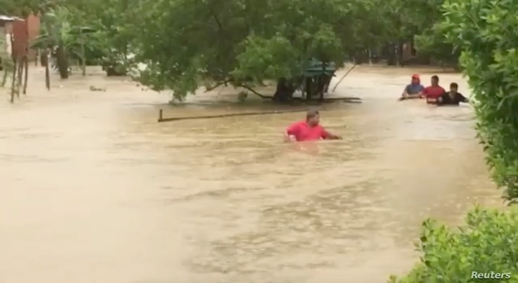 People wade in floodwaters caused by Hurricane Iota in Cartagena, Colombia in this still image taken from social media video…