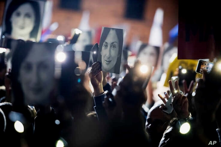 FILE - People hold pictures of journalist Daphne Caruana Galizia, who was slain in October 2017, as they protest in Valletta, Malta, Nov. 29, 2019.