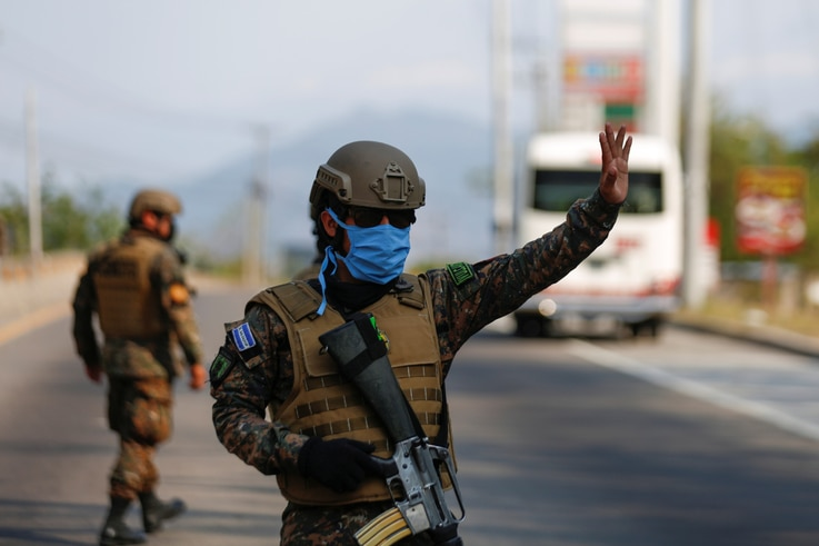 A soldier stops a car at a checkpoint during a quarantine throughout the country, as the government undertakes steadily…