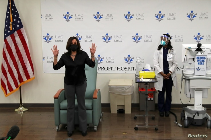 U.S. Vice President-elect Kamala Harris gestures after receiving a dose of the Moderna COVID-19 vaccine at United Medical…