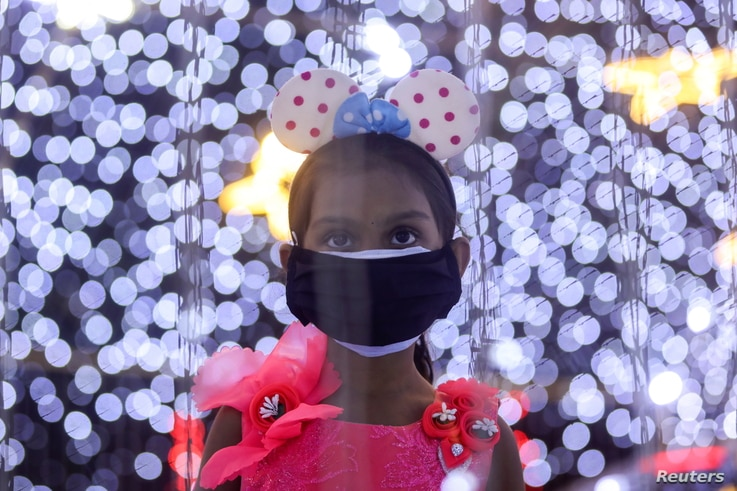 A girl wearing a protective mask looks at decorations at a mall on New Year's Eve, amid the spread of the coronavirus disease …