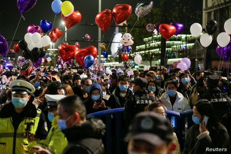 Police officers stand guard as people gather to celebrate the arrival of the new year during the coronavirus disease (COVID-19)…