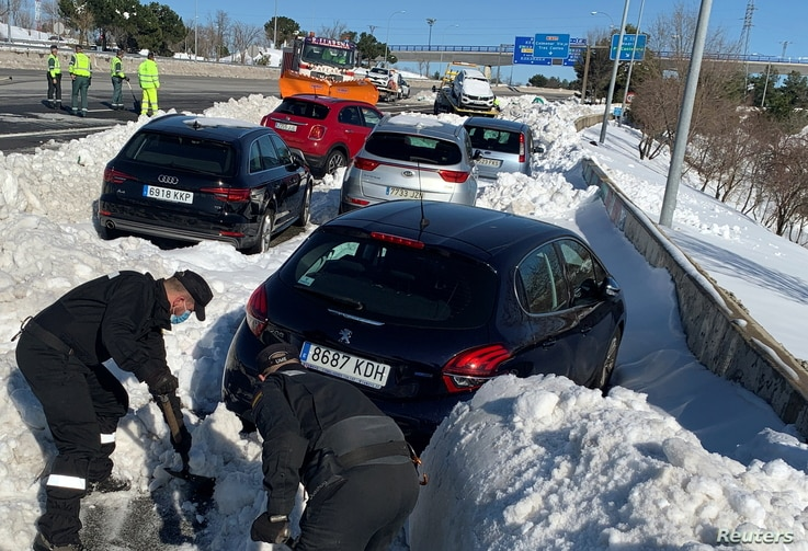 Members of Spain's military unit (UME) shovel snow to open a pass next to cars accumulated on M-40 highway after heavy snowfall…