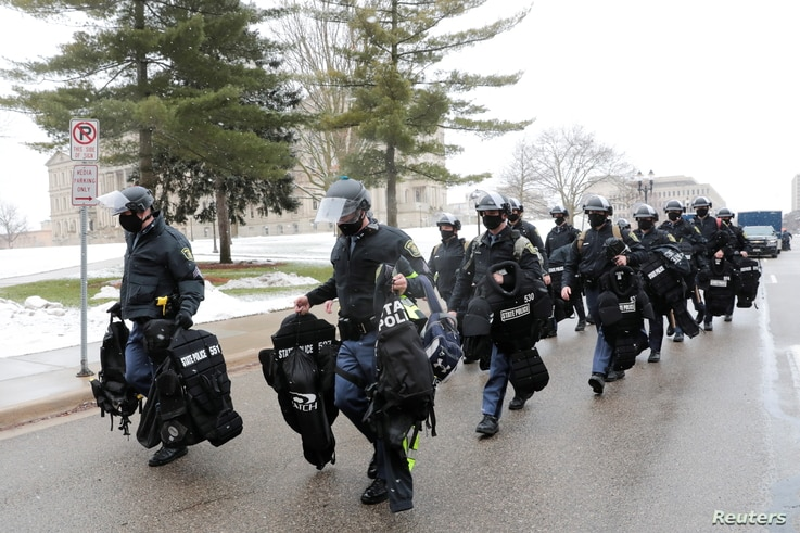 Members of the State police arrive at the Michigan state Capitol in Lansing, Michigan, U.S. January 17, 2021. REUTERS/Rebecca…
