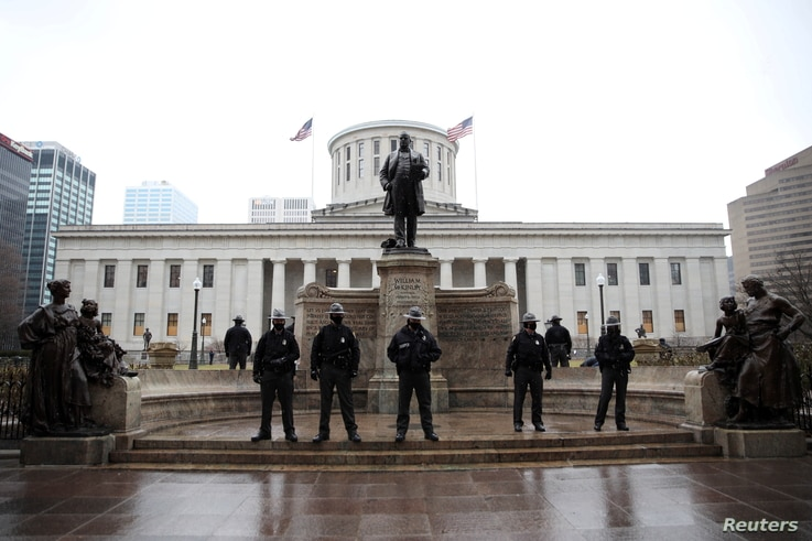 Law enforcement officers guard the state house as supporters of U.S. President Donald Trump protest against the election of…