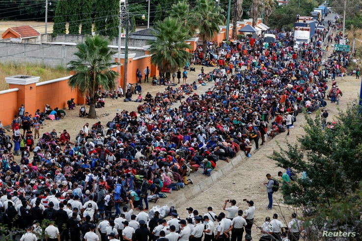 Hondurans taking part in a new caravan of migrants, set to head to the United States, gather in front of police officers…