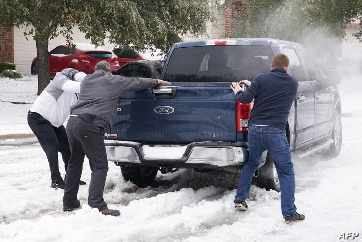 Residents help a pickup driver get out of ice on the road in Round Rock, Texas, on February 17, 2021, after a winter storm. -…