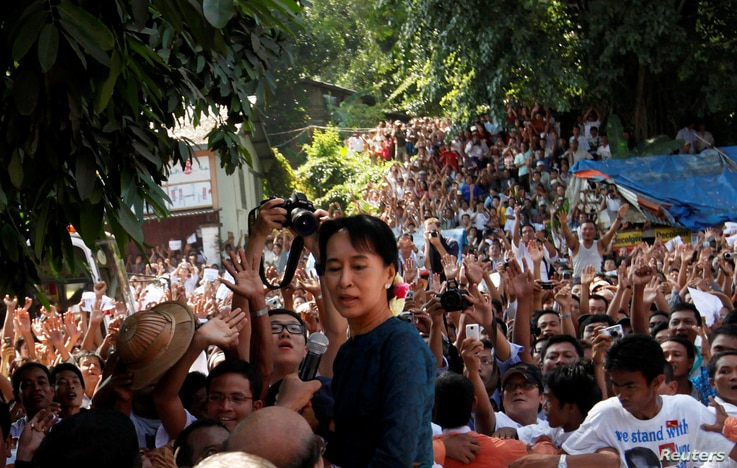 FILE PHOTO: Aung San Suu Kyi stands among supporters gathered to hear her speech outside the headquarters of her National…