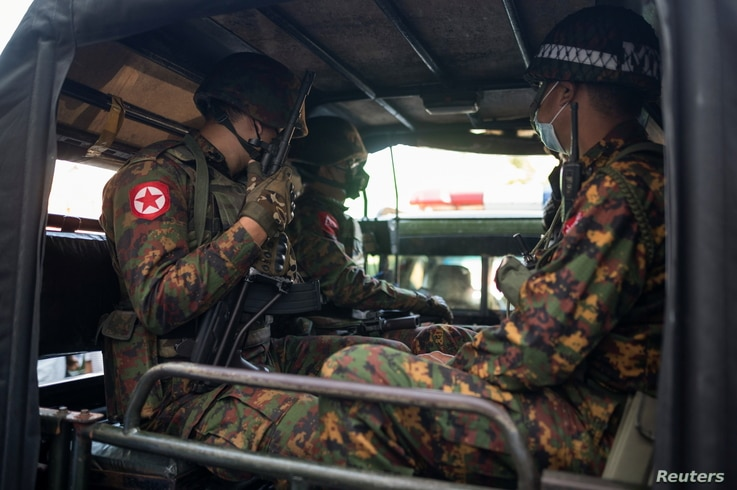 Myanmar soldiers sit inside a vehicle as they guard in front of a Hindu temple in the downtown area in Yangon, Myanmar,…