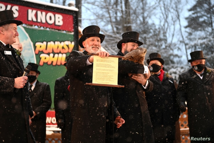 Groundhog Club Inner Circle Vice President Tom Dunkel holds the scroll with Phil's forecast of six more weeks of winter during…