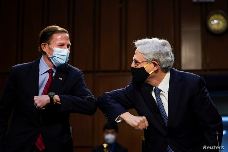 (L-R) Sen. Richard Blumenthal (D-CT) gives an elbow bump to Attorney General nominee Merrick Garland as they arrive for Garland…