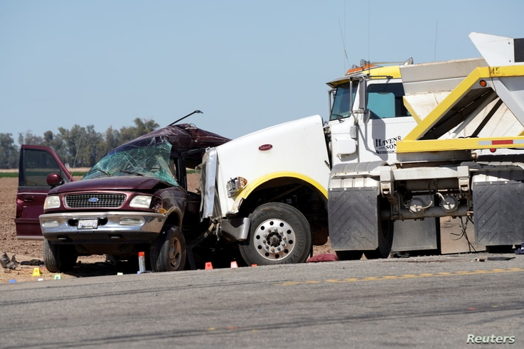The scene of a collision between a sport utility vehicle (SUV) and a tractor-trailer truck is seen near Holtville, California,…