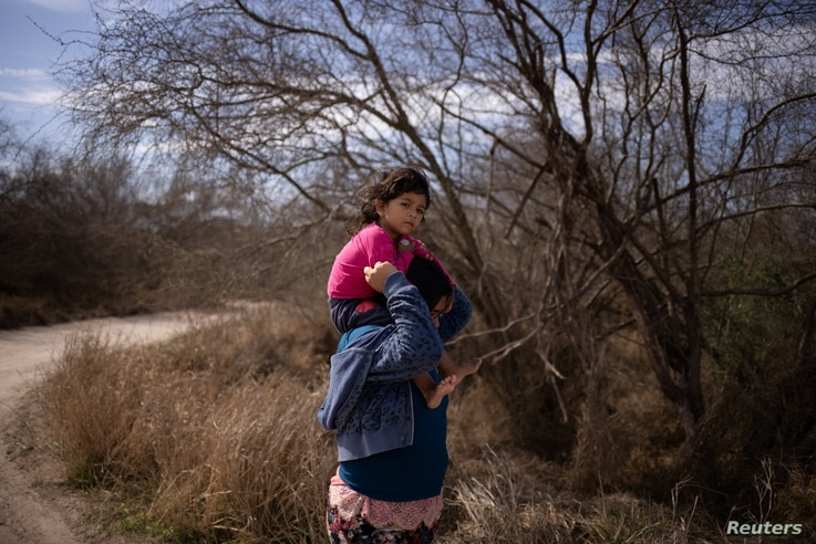 Maria, 4, from El Salvador, is held by her mother Loudi as they walk down a dirt road after crossing the Rio Grande River into…