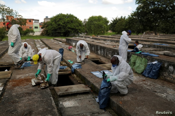 Gravediggers wearing protective suits close bags with bones during exhumations to open space on cement graves as new burials…