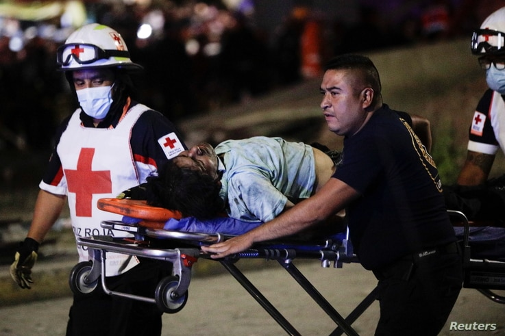 Rescuers wheel an injured person on a stretcher a site where an overpass for a metro partially collapsed with train cars on it…