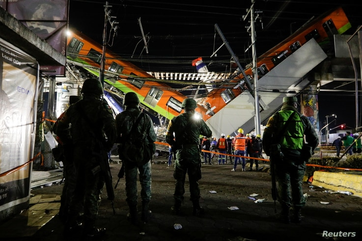 Soldiers stand as rescuers work at a site where an overpass for a metro partially collapsed with train cars on it at Olivos…