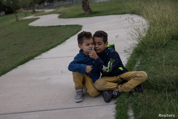 James, 5, and Denis, 9, asylum-seeking migrant brothers from Honduras, sit in a park as they await with others to be…