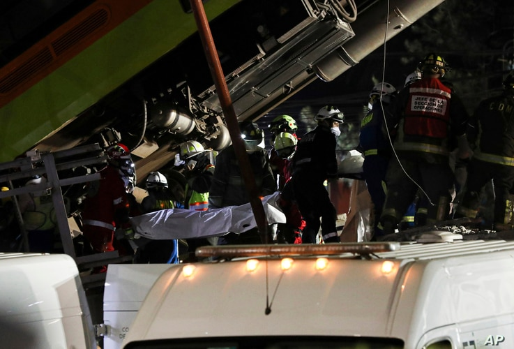 Rescue personnel retrieve bodies from the scene of an accident where subway cars fell after a section of Line 12 of the subway…