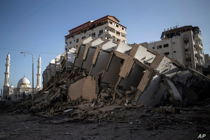 The remains of a building destroyed by Israeli airstrikes on Gaza City, Wednesday, May 12, 2021. Rockets streamed out of Gaza…