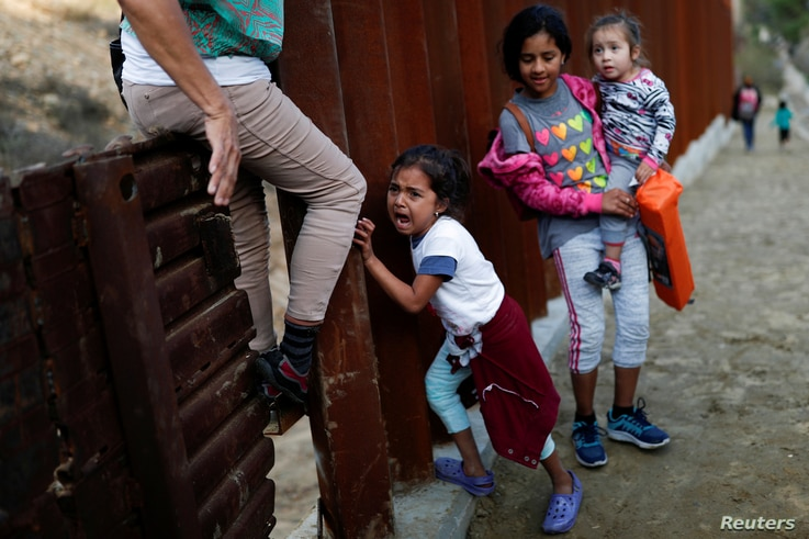 A migrant girl, who is part of a caravan of thousands from Central America trying to reach the United States, cries next to the…