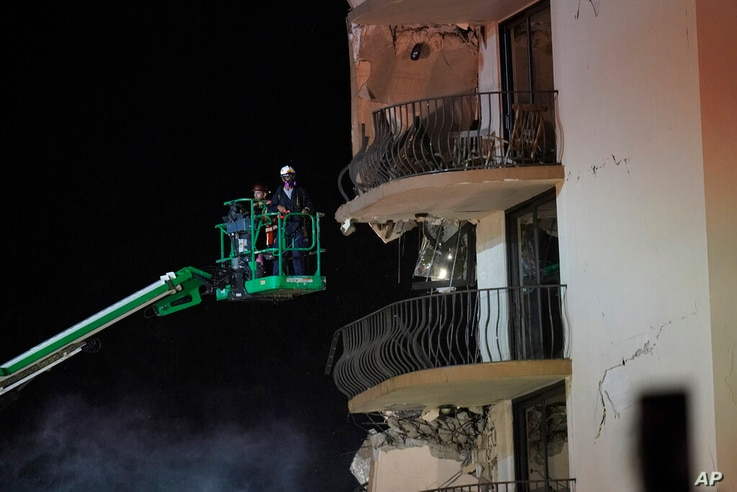 Workers use a lift to investigate balconies in the still-standing portion of the building, as rescue efforts continue where a…