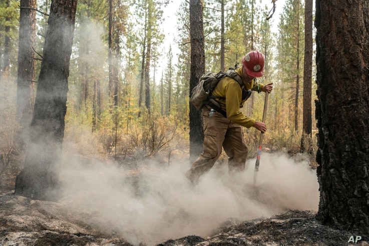Firefighter Garrett Suza, with the Chiloquin Forest Service, mops up a hot spot on the North East side of the Bootleg Fire,…