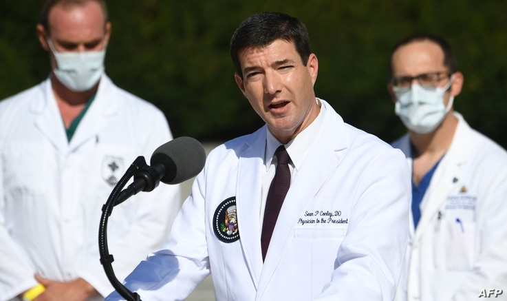 White House physician Sean Conley (C) answers questions surrounded by other doctors, during an update on the condition of US…