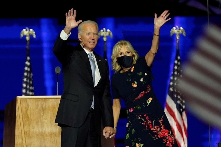 TOPSHOT - US President-elect Joe Biden with his wife Jill Biden salute the crowd on stage after delivering remarks in…