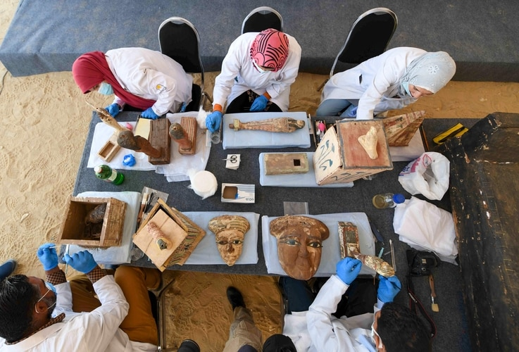 TOPSHOT - Archaeologists clean statues and funerary masks during the unveiling of an ancient treasure trove of more than a 100…