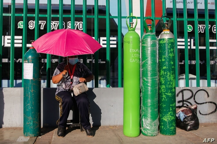 CORRECTION - A woman waits under an umbrella next to a line of oxygen tanks in a queue of up to 200 people who camp to refill…