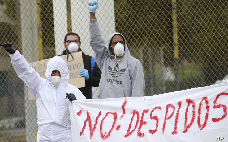 """Workers who were fired from their jobs hold a banner with a message that reads in Spanish: """"No Layoffs"""", during a protest…"""