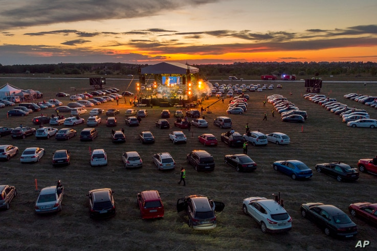 Fans attend the drive-in concert of the Hungarian rock band Tankcsapda at the Debrecen International Airport in Debrecen,…