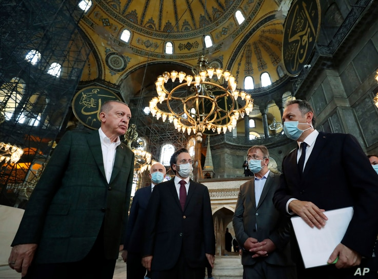 Turkey's President Recep Tayyip Erdogan, left, listens to an official as he visits the Byzantine-era Hagia Sophia, one of…