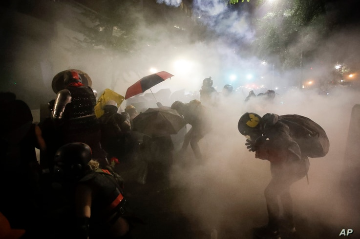 Federal officers launch tear gas at a group of demonstrators during a Black Lives Matter protest at the Mark O. Hatfield United…