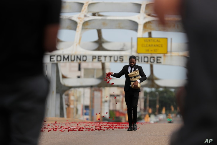 A man places flower petals on the Edmund Pettus Bridge ahead of Rep. John Lewis' casket crossing during a memorial service for…