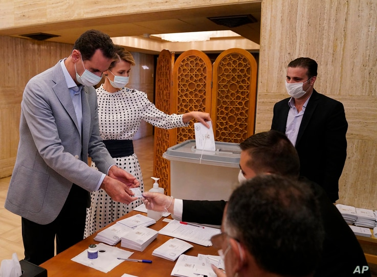 In this photo released on the official Facebook page of Syrian Presidency, Syrian President Bashar Assad and his wife Asma vote…