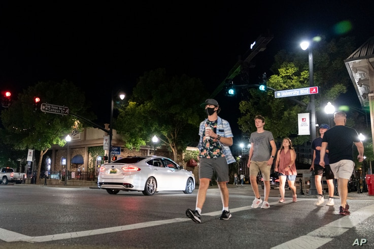 People make their way along The Strip, the University of Alabama's bar scene, Saturday, Aug. 15, 2020, in Tuscaloosa, Ala. More…