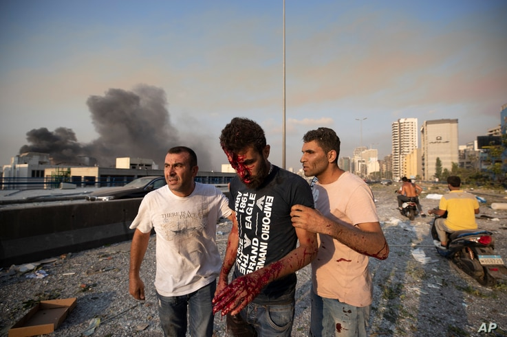 People help a man who was wounded in a massive explosion in Beirut, Lebanon, Tuesday, Aug. 4, 2020. Massive explosions rocked…