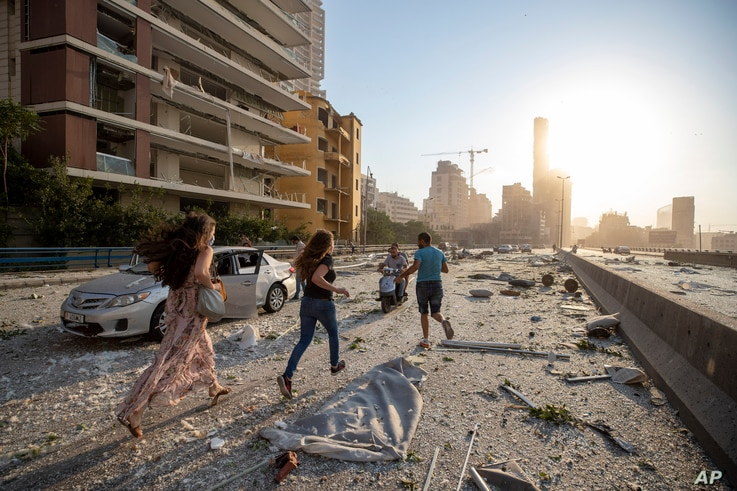 People run in the aftermath of a massive explosion in Beirut, Lebanon, Tuesday, Aug. 4, 2020. (AP Photo/Hassan Ammar)