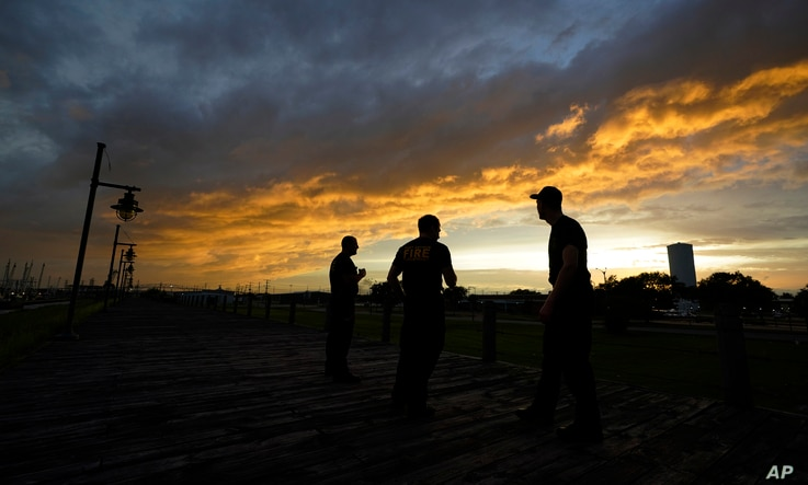 Port Arthur firefighters stare at a sea wall at sunset as they wait for Hurricane Laura to make landfall, Wednesday, Aug. 26,…