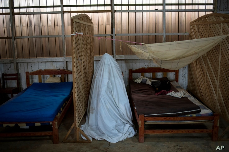 Sara Magin, who suffers from COVID-19 symptoms, sits inside a tent constructed from a bedsheet as she receives an herbal vapor…