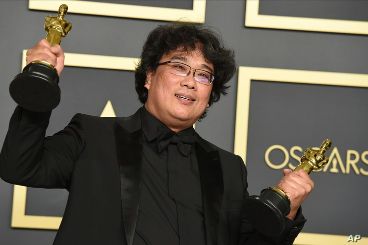 """Bong Joon Ho poses in the press room with the awards for best director for """"Parasite"""" and for best international feature film…"""