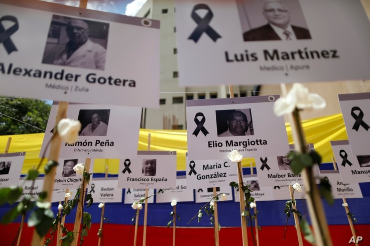 The photos of health workers who have died of COVID-19 stand on display for a ceremony in their honor, organized by fellow…