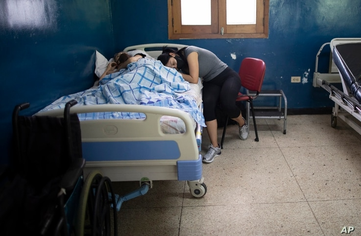 A woman leans on the side of a relative suffering cancer at the Luis Razetti Oncology hospital in Caracas, Venezuela, Wednesday…