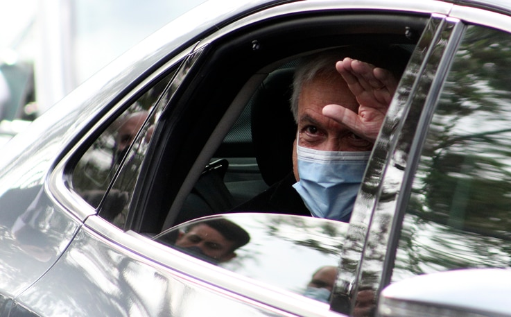 Chilean President Sebastian Pinera waves as he arrives a polling station during a referendum to decide whether the country…
