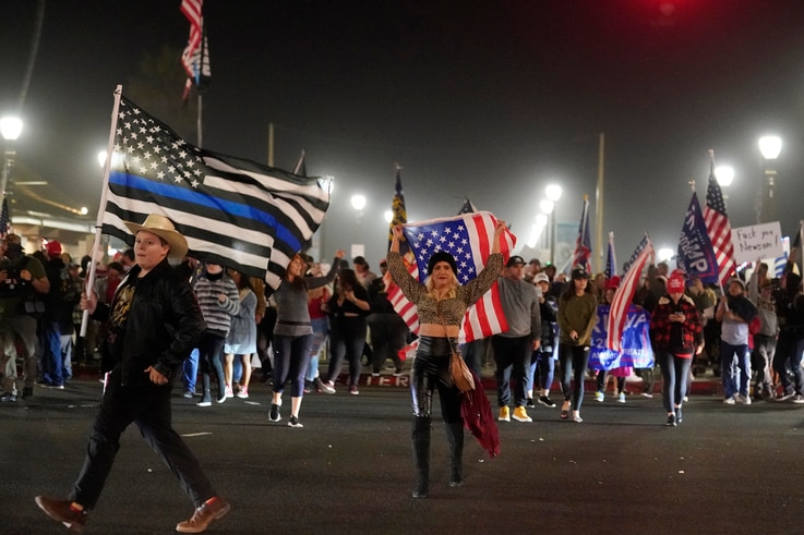 Demonstrators march across Pacific Coast Highway Saturday, Nov. 21, 2020 during a protest against a stay-at-home order amid the…
