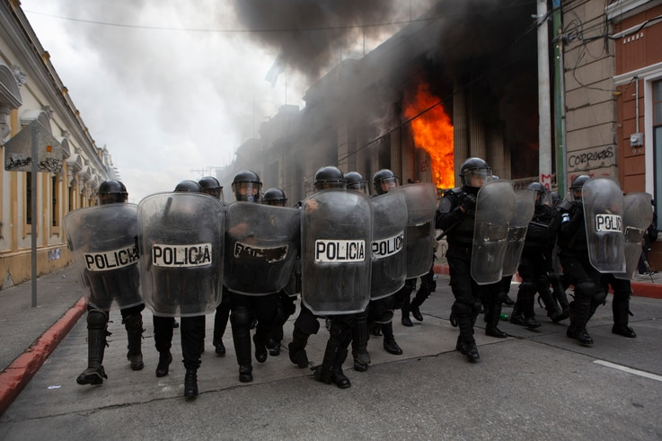 Riot police form a cordon as flames shoot out from the Congress building after protesters set a part of the building on fire,…